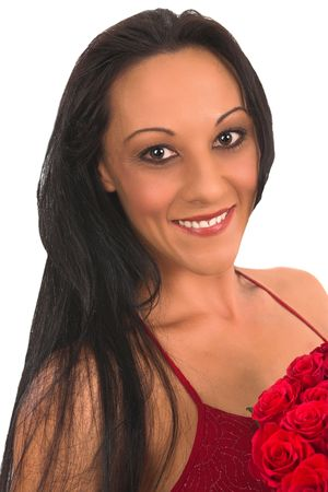 A beautiful  middle aged brunette dressed in a red evening dress is holding a bunch of red roses on valentine day