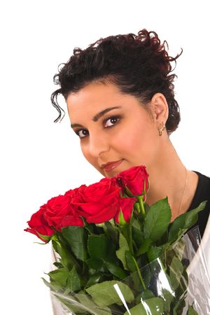 a beautiful young brunette is smelling her red valentine roses.