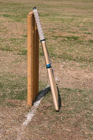a cricket bat leaning against the wickets on a pitch, summer sport scene Stock Photo