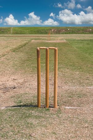 a full length view of a grass cricket pitch in summer with both sets of wickets and bails setup. Stock Photo