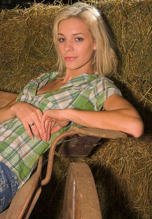 a beautiful blond lady is leaning backwards onto bales, she is sitting on an old horse cart Stock Photo