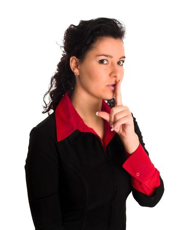 a beautiful lady in a black jacket is pointing with her finger on her lips telling others to be queit. Shoosh. Stock Photo
