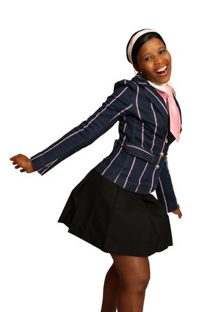 A young African American school girl is smiling as her uniform is blown in the wind