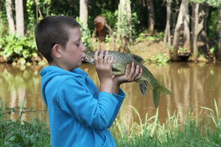 a young boy is very happy after catching his fish and actually kisses this yellowtail fresh water fish on the mouth beside the river