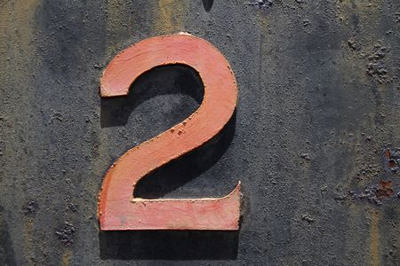 a number 2 two made of steel that is a faded red colour mounted on a rusted steel background frokm a train.