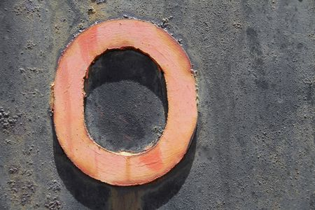 a red metal rusted and faded number zero or nul on the side of a rusted old train. Stock Photo