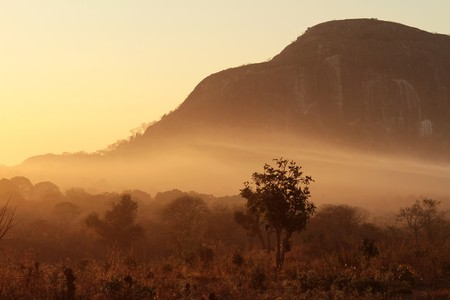 A beautiful typical African sunrise, fog and mist being colored orange by the suns rays