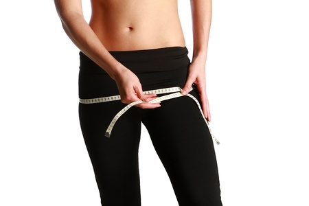 Photo of a fit and healthy young lady measuring her waist with a tape measure in centimeters and millimeters. She has her black gym exercise outfit on. Isolated image on white.
