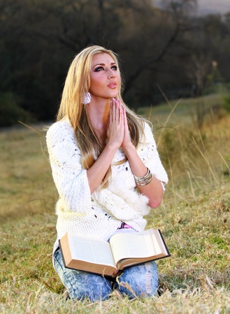 A young blonde lady is sitting on her knees, kneeling and praying with the Bible open on her lap