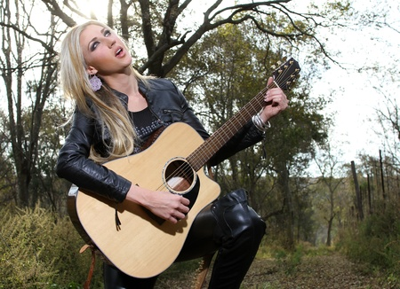 A beautiful blonde young lady is playing a guitar and singing in the forest, she could also be worshipping