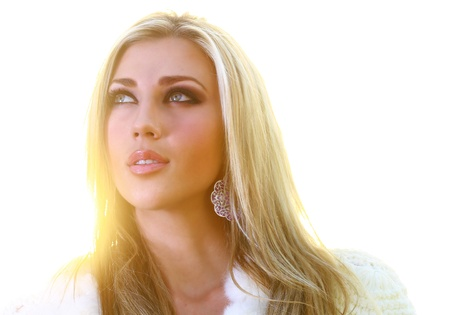 A beautiful young blonde lady is looking skywards with golden sun in her hair. She has a prayerful attitude.