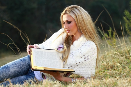 A beautiful young blonde lady in her twenties is reading her Bible outside ina park