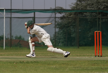 A young school boy is playing a square drive shot with a beautiful follow through finishing it perfectly. Stock Photo