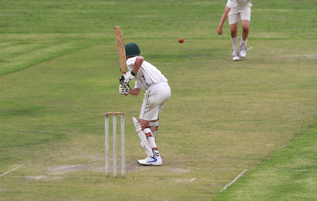 bails: A young school boy cricket player is a attacking the cricket ball bowled by the bowler on a lush green cricket pitch in South Africa.