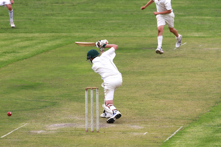 A youth cricket player or young teenage boy is driving a cricket ball through the covers.