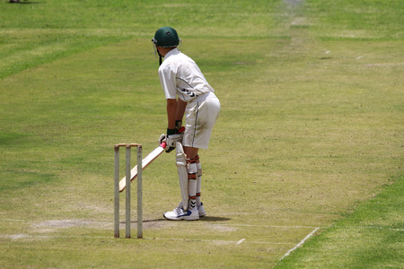 A young school boy cricket player is preparing to attack the ball.