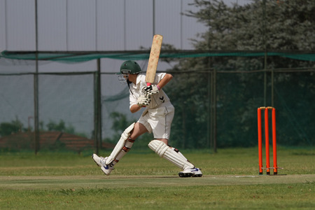 bails: A young school boy playing cricket is tepping out on the front foot attacking the ball