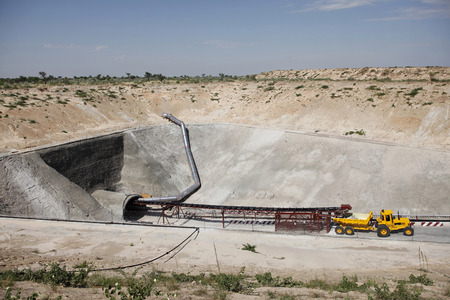 duty belt: A mining vehicle is parked just outside on the entrance of an inclined diamond mine shaft in the desert