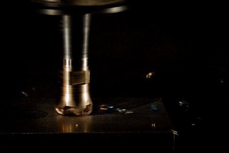 splinters: Milling cutter machine work with Splinters flying off on a dark background, color version