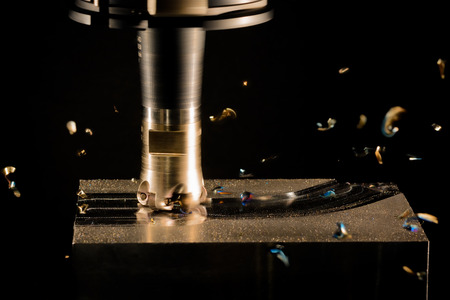 Milling cutter machine work with Splinters flying off on a dark background, color version