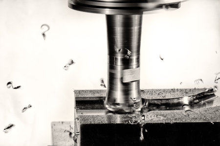 splinters: Milling cutter machine work with Splinters flying off on a light background, monochrome version