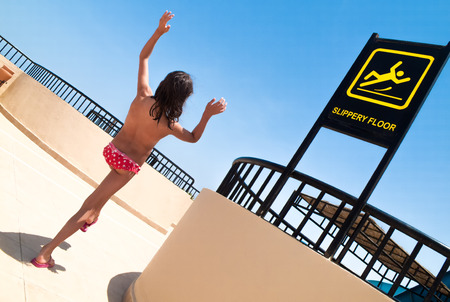 Signs warning of slippery floors in the swimming pool and slipping a child Stock Photo