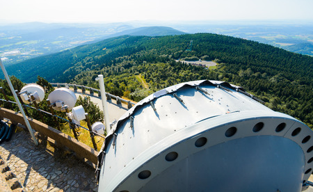 shortwave: The system of telecommunication aerials high above the landscape. The background is extensive hilly landscape.