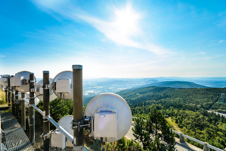 routing: The system of telecommunication aerials high above the landscape. The background is extensive hilly landscape, blue sky with clouds and sun rays in the frame.