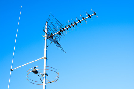 polarization: simple antenna mast with antennas to receive digital TV and radio signals, DVB-T, DVB-T2 and FM (horizontal polarization) including delayed lightning rod. The background is pure blue sky.