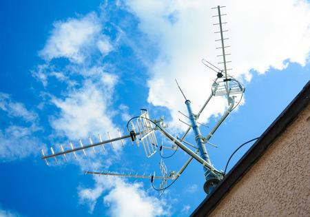 Antenne complexe pour recevoir des signaux de télévision et de radio numériques sur le mât d'antenne - une antenne de télévision commune (pour recevoir des signaux: DVB-T, DVB-T2, DAB, FM à partir de 4 directions, le soleil dans le cadre) Banque d'images - 51116087