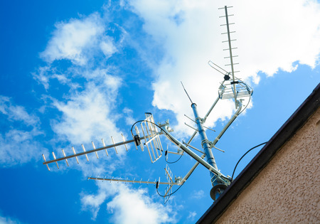 complex antenna to receive digital TV and radio signals at the antenna mast - a common TV antenna (to receive signals: DVB-T, DVB-T2, DAB, FM from 4 directions, the sun in the frame)