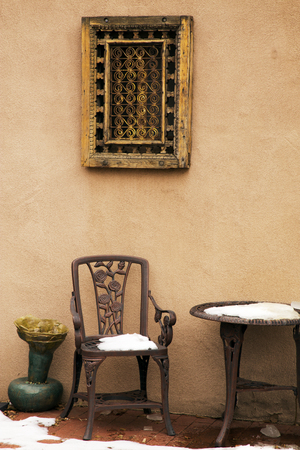 Cast Iron Chair and Table Under A Decorative Window Covering, Santa Fe, New Mexico