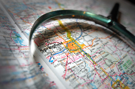 A magnifying glass pictured over a map of Springfield, MO and the Ozarks.