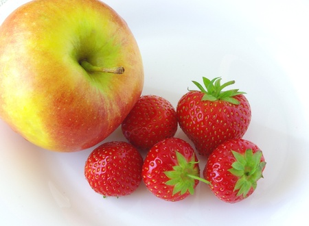 Apple and strawberries on white dish