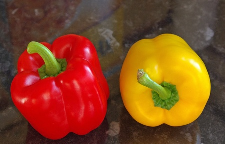 Red and yellow peppers on work surface