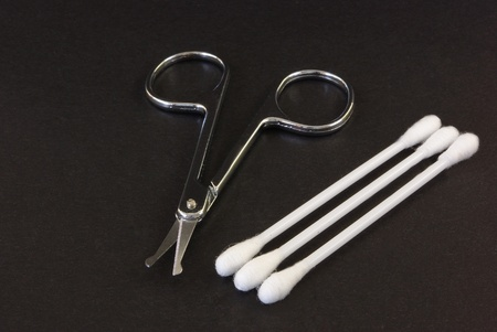 nail scissors: Nail scissors and cotton buds on black background Stock Photo
