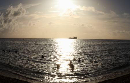 Abstract view of bathers in ocean at sunset, Mon Choisy Mauritius