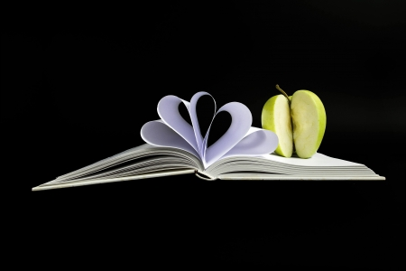 sliced apple: Open book with sliced apple Stock Photo