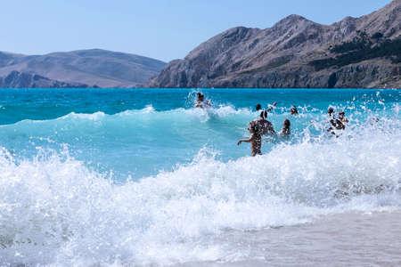 Fun play with waves on beach in Baska voda on Island Krk