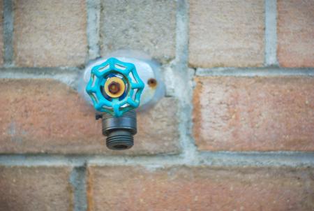 spigot: tap water spigot on brick wall, aqua blue green valve