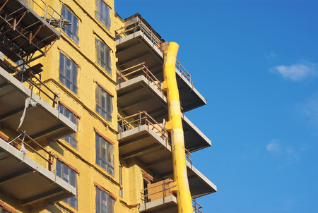 downfall: yellow building in construction with downfall slide on blue sky