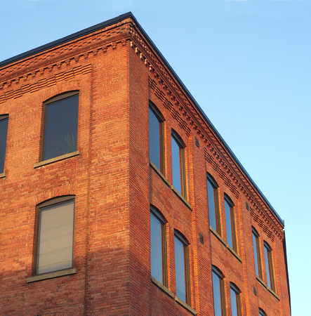 brick building: red brick office building corner in sunlight blue sky Stock Photo