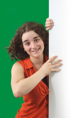 girl holding board with green screen background, orange shirt and white cardboard