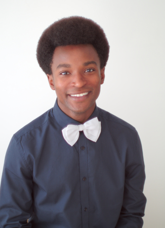 african business: young man studio portrait smile black shirt and bow tie