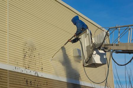 Limpiar una pared con un chorro de agua a presión Foto de archivo