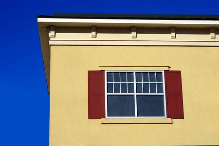 yellow beige wall window roof blue sky facade