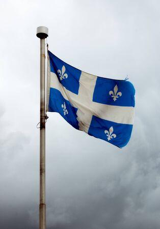 quebec flag fluttering in the wind on blue sky