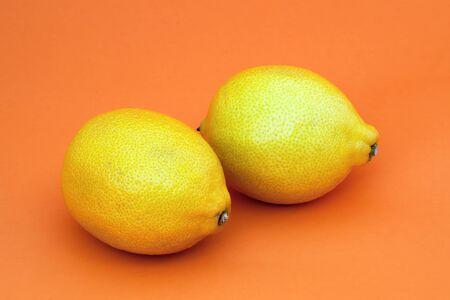 yellow lemons on orange background healthy fruits  Stock Photo