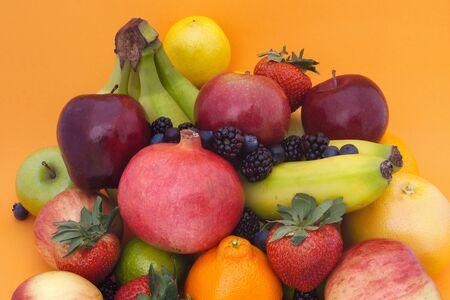 many fruits orange background still life organic healthy eating Stock Photo