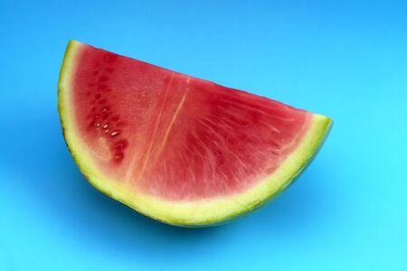 watermelon slice pink juicy fruit on blue background Stock Photo